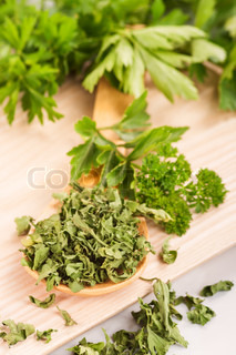 Dried herbs parsley and celery on a wooden spoon.