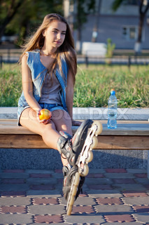 smiling roller girl sitting on the bench