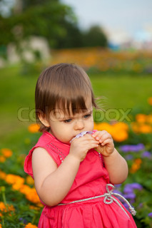 Sweet Blonde Girl Smelling Flowers On The Meadow Stock