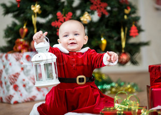 baby girl dressed as Santa Claus atChristmas tree with lamp
