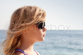 Little blond girl profile portrait with sunglasses on the summer sea coast