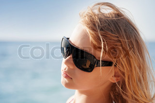 Little blond girl portrait with sunglasses on the summer sea coast