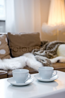 Two coffee cups on the table with sofa with fur cover on it