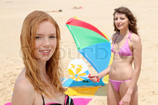 Portrait Of Two Girls Playing Rackets On The Beach