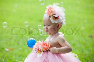 Little girl in flower dress playing ball and bubble