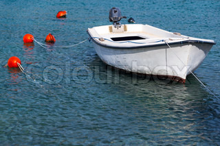 White wooden fishing boat floats moored in Adriatic sea water, Montenegro