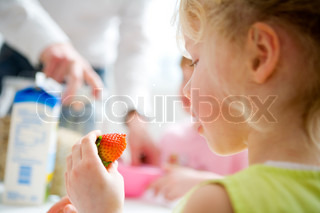 A young caucasian girl eating strawberry