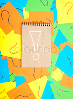 Pile of colorful paper notes with question marks and note book with exclamation mark