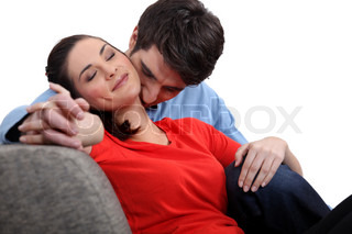 Man and woman tenderly hugging on a sofa