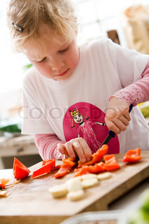 A young caucasian girl slicing red peppers
