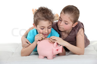 Kids putting coins in a piggy bank
