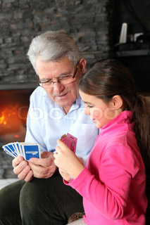 Grandfather and granddaughter playing cards
