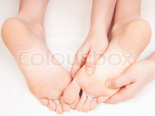 therapist doing a foot massage pressing reflexology zones on the woman's right foot