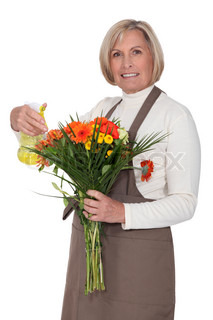 A florist spraying flowers with water