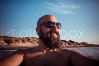 long bearded man in the beach with sunglasses
