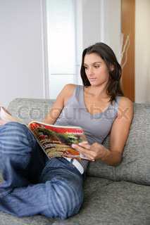 woman sat on a couch reading magazine stock photo colourbox. Black Bedroom Furniture Sets. Home Design Ideas