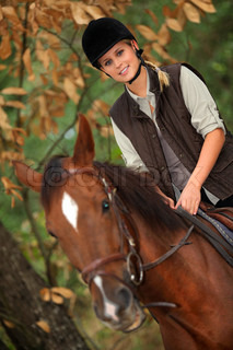 Young girl horseriding through the forest