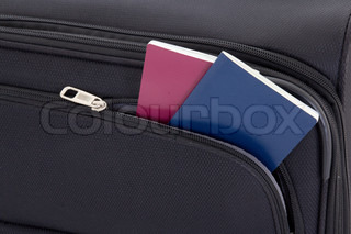 black travel suitcase and two passports