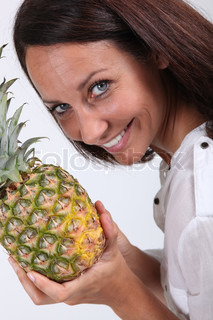 beautiful lady all smiles holding pineapple
