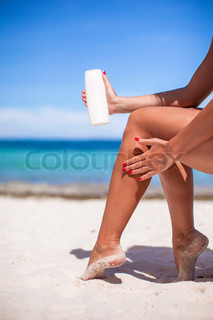 Woman apply cream on her smooth tanned legs at tropical beac
