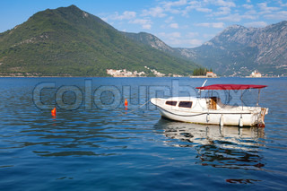 Small white pleasure boat floats moored in Perast town, Kotor Bay, Montenegro