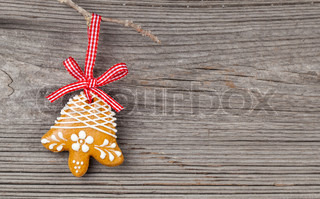 Gingerbread cookie hanging on wooden background Christmas decoration