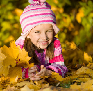 smiling cute girl against the leaves