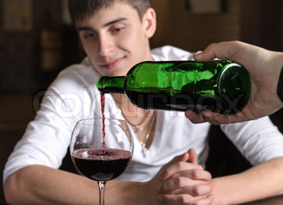 Barman or waiter pouring red wine