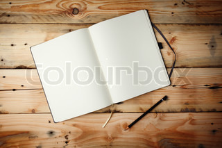 Open blank notepad with empty white pageslaying on a wooden table