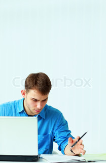 Young pensive casual businessman reading document at office