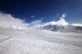 Ski slope and mountains in clouds