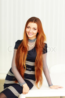 Young beautiful cheerful woman leaning at the table