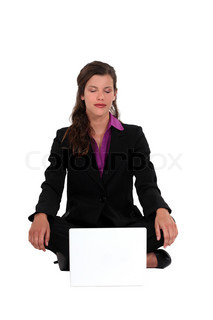 A businesswoman in a lotus position