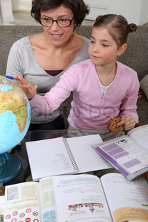 Woman looking at a globe with a little girl