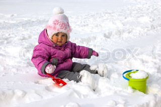 Little girl sitiing and playing with snow