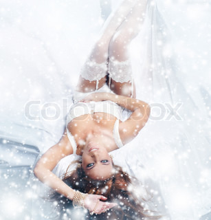 Young and sexy redhead woman in white lingerie over the winter background with the snow