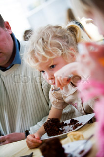 A young caucasian girl eating a piece of chocolate cake