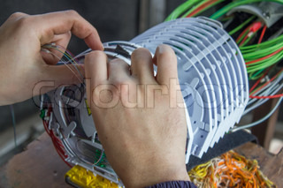 Fibre optic technician hands sorts optic cables