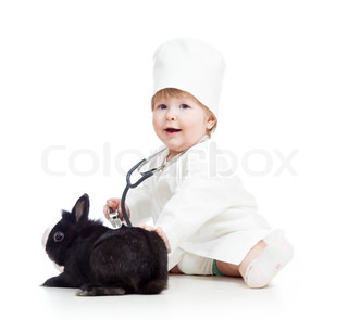 kid with clothes of doctor playing with pet bunny