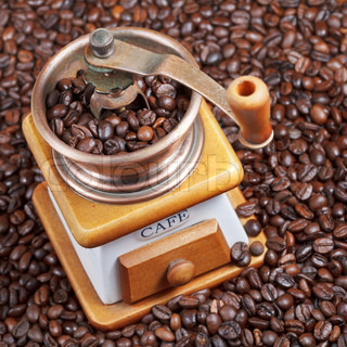 retro manual coffee mill on roasted beans