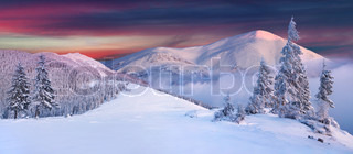 Panorama of snow covered peaks of the mountains in the morning mist