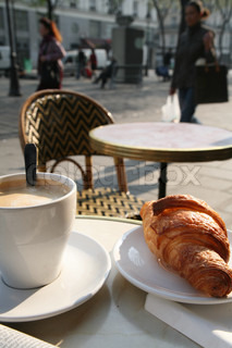 cup of coffee and a croissant on a plate in an outdoor cafe
