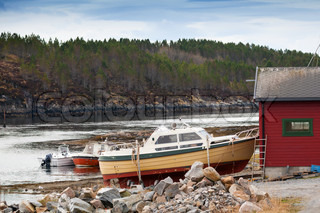 Small motor boats stand on the coast in Norway