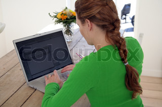 A woman uses her laptop in a dining table