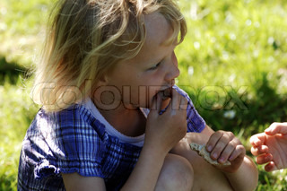 Little blond girl eating a snack in the garden