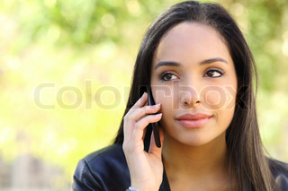 Portrait of a beautiful woman on the mobile phone in a park