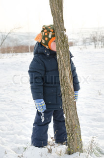 Little boy sulking and hiding behind a tree trunk