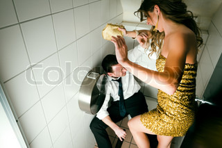 Young couple fight on a party in the toilette