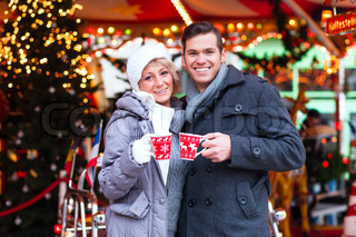 Couple drinking spiced wine on Christmas market
