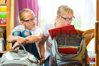 Girls doing homework and packing school bags